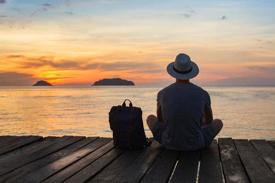 wanderlust travel, tourist with backpack sitting near the sea, man enjoying sunset, solo traveler backpacker in Asia