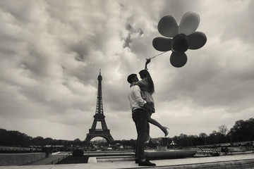 vintage photo of Paris with affectionate couple holding balloons near Eiffel tower, retro style view