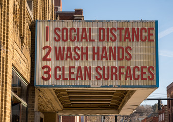 A photo illustration of a movie cinema billboard with three basic rules to avoid the coronavirus or Covid-19 epidemic of wash hands, maintain social distance and clean surfaces
