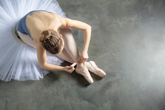 Top view at ballet dancer tying slippers around her ankle