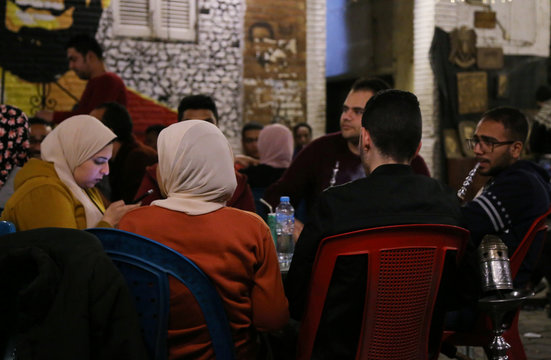 Egyptian youth smoke shisha water-pipes outside a coffee shop in Cairo