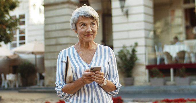 Caucasian beautiful old woman standing in center city and tapping message on smartphone. Grandmother using cellphone while typing sms. Senior nice female texting and scrolling on phone outdoors.