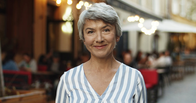 Portrait of beautiful senior Caucasian woman with grey hair looking straight at camera and smiling cheerfully outdoor in town. Close up of old lady with smile standing on street.
