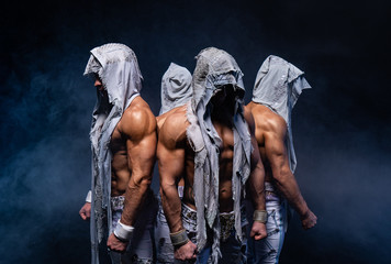 Four muscular gothic man standing shirtless on black background. Concept of power, strength and heroism