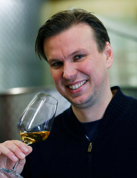 Winemaker Zimmerle holds a glass with fermented must of frozen ice wine grapes at his vineyard in Korb
