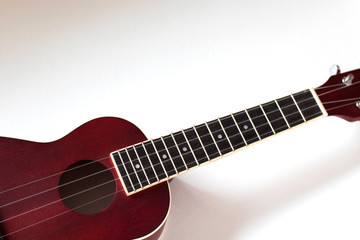 A red wooden ukulele crosses a white background from left to right. Flatlay. The photo expresses...