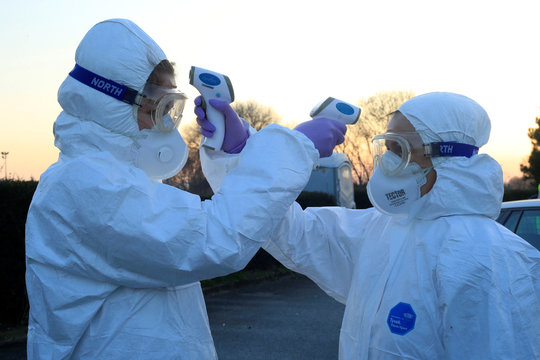 Medical staff use thermometers during checks for coronavirus (COVID-19) at the border crossing with Italy in Vrtojba