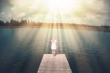 Magical sunlight with beams with a woman standing on wooden pier.