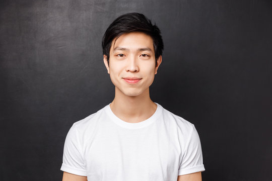 Close-up portrait of smiling friendly-looking young asian male model in white t-shirt, looking at camera and grinning, standing over black background, concept of people emotions and lifestyle