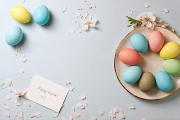 colorful eggs on plate, greeting card and flower blossoming branch on the table; easter celebration concept.