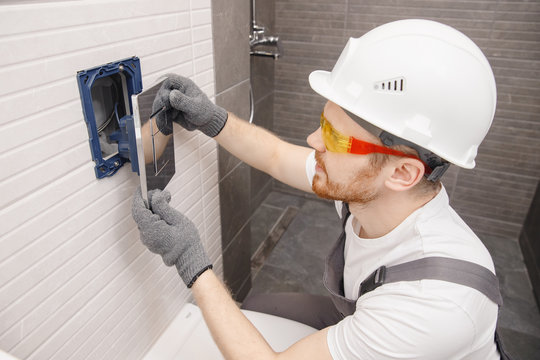 Plumber installing button for toilet bowl in restroom, work in bathroom