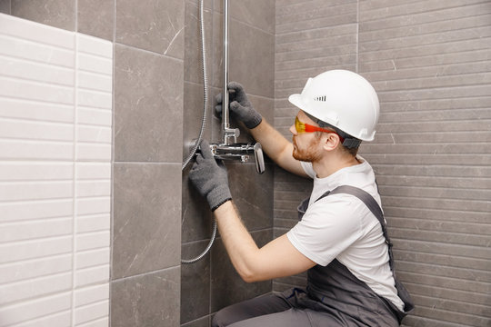 Plumber installing water taps shower stall, work in bathroom