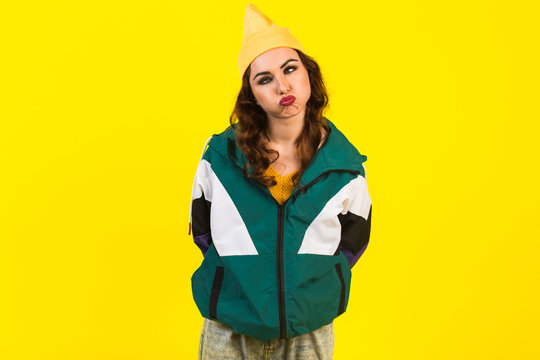 Modern beautiful girl in oversized sports jacket, hat and jeans, Billie Eilish style, back in the 90s, 2000s. Posing in the studio on a yellow background, strong funny emotions