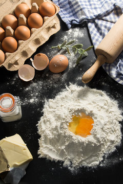 eggs, flour, butter and rolling pin on black messy kitchen table