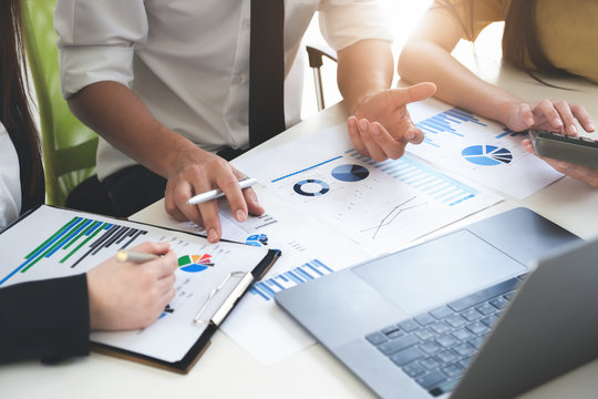 A male business consultant describes a marketing plan to set business strategies for women business owners with using calculator. business planning and business researching concept.