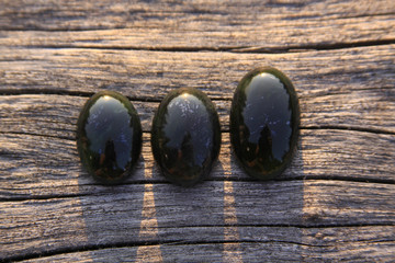 Three black jade translucent gemstones on wood