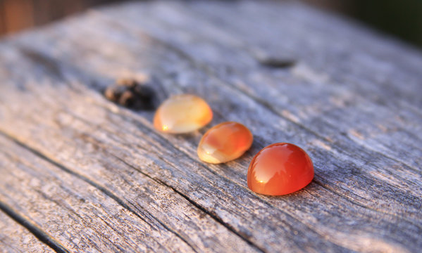 Three chalcedony agate gemstones on wooden background