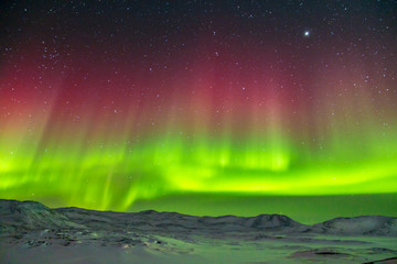 Spectacular red and green Aurora Borealis Northern Lights in Greenland
