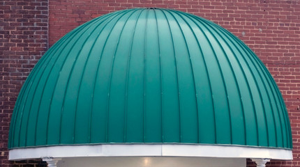 Green dome shaped awning entrance to urban hotel.