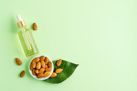 flat lay almond oil and whole nut for skincare, massage, cooking on green background.