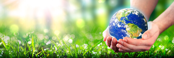 Hands Holding Planet Earth In Lush Green Environment With Sunlight - Earth Day Concept - Some Elements Of This Image Were Provided By NASA