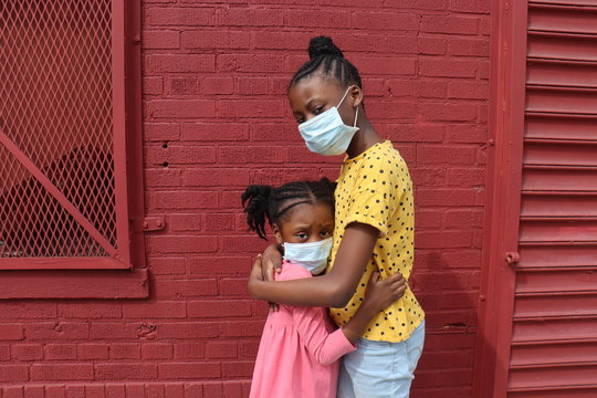 African American Girls Hugging Wearing Surgical Masks