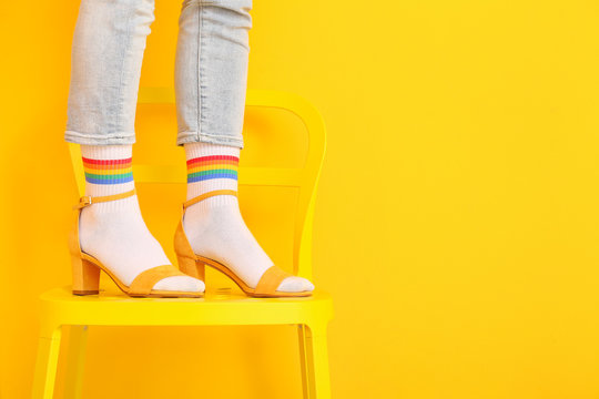 Legs of young woman in socks and sandals standing on chair against color background