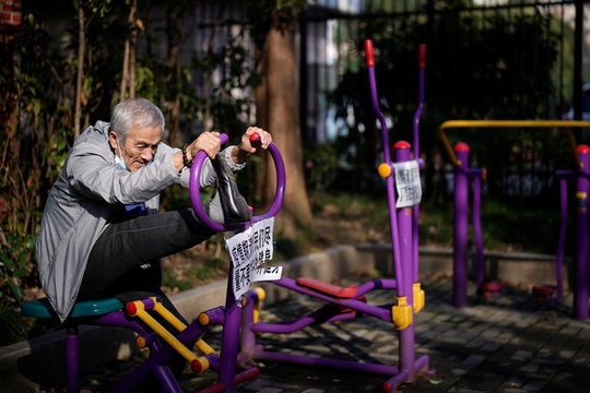 Elderly man works out on an exercise machine with a sign advising residents to avoid exercising outdoor during the novel coronavirus outbreak, at a park in Shanghai