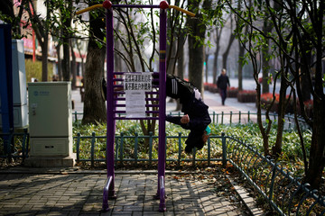 Woman works out on an exercise machine with a sign advising residents to avoid exercising outdoor during the novel coronavirus outbreak, at a park in Shanghai