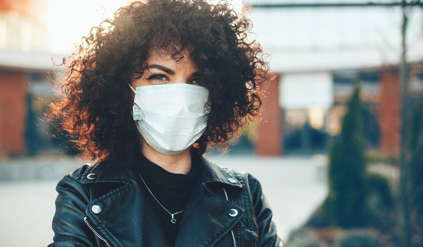 Curly haired caucasian lady posing outside while wearing a protective mask