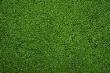 Green shiny background. Green uneven color. A sheet of dark green crumpled paper with natural light. Fragment of a crumpled sheet of green paper with highlights Wall mural