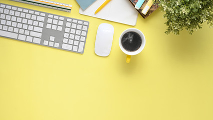 Top view image of yellow color working table with office equipment putting on it. Flat lay keyboard, wireless mouse, coffee cup, notebook, potted plant, ruler and marker pen.