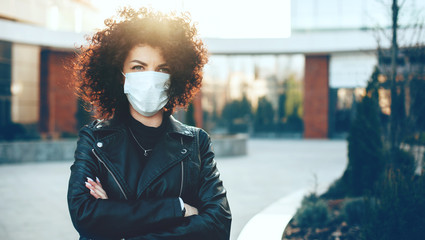 Caucasian woman posing with crossed hands while wearing an anti flu mask and looking at camera