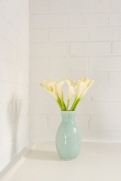 Close up vertical view of white calla lilies in green vase on table against painted brick wall