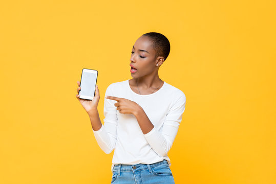 Young African American woman looking and pointing at mobile phone isolated on yellow background