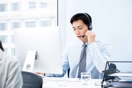 Focused handsome Asian man working in call center office as a telemarketing operator