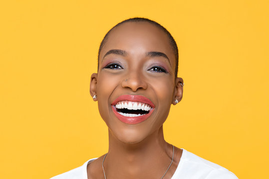 Close up portrait of friendly happy African American woman smiling on isolated colorful yellow background