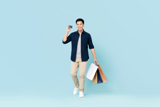Handsome young Asian tourist man carrying bags shopping with credit card isolated on light blue background