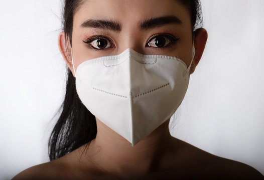Close up of a asia woman putting on a respirator N95 mask to protect from airborne respiratory diseases as the flu covid-19 coronavirus ebola PM2.5 dust and smog