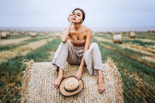 Barefoot brunette in linen pants and bare shoulders sitting on a hay bales in warm autumn day. Woman looking at camera. Behind her is a wheat field