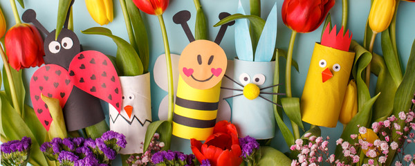 Happy easter kindergarten decoration concept - rabbit, chicken, egg, bee from toilet paper roll tube, fresh tulips. Simple diy. Eco-friendly reuse recycle decor, daycare paper craft