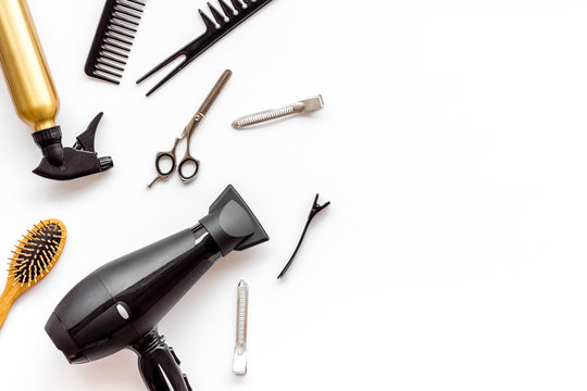 Professional hairdressing set with combs and hairdryer on white background top-down frame copy space
