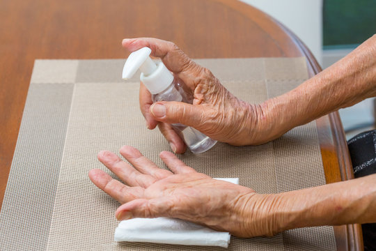 Elderly woman applying alcohol gel cleaning hands to helping protect from coronavirus covid-19