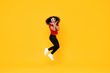 Happy fashionable African American girl jumping in mid-air with hands on chin isolated on yellow background