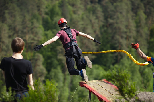 Extreme athlete, tied to a safety rope, jumped into the void after a take-off on a wooden platform, back view. Ropejumping.
