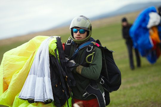 Skydiver, a tandem instructor, holds a parachute dome in his hands after performing a jump in tandem with the passenger, close-up. Parachute jump.