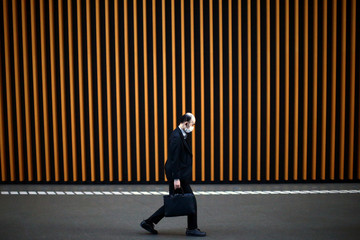 Man, wearing protective mask following an outbreak of COVID-19, walks inside Tokyo International Forum in Tokyo