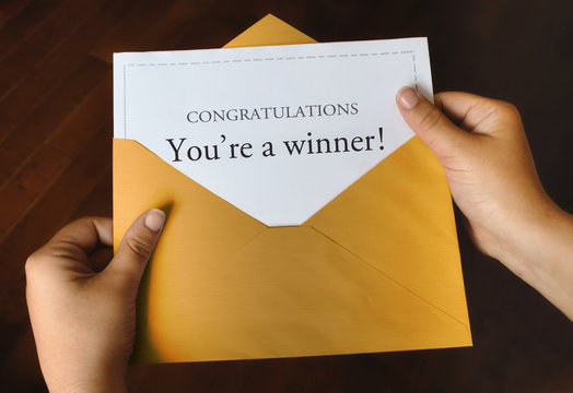 An open shiny gold envelope with a letter that says Congratulations You're a winner! with female hands holding it up