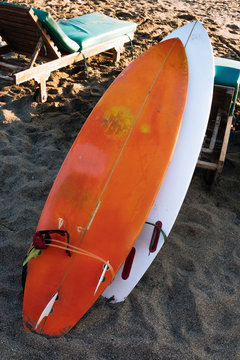 Two white and yellow surf boards lying on sandy beach by ocean..Bali.Indonesia. Surf boards on sandy beach for rent. Surf lessons on Weligama beach, Sri Lanka