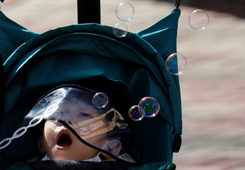 A boy wearing a hat with a protective screen blows soap bubbles at a park in Daegu
